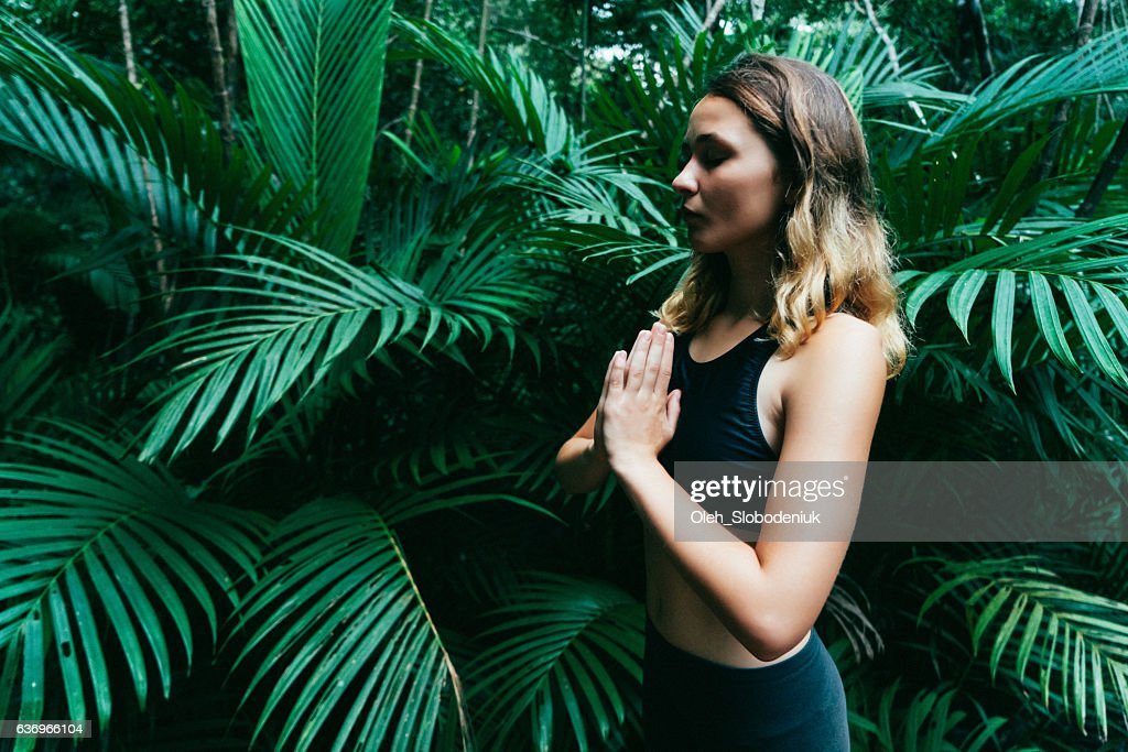 Woman doing yoga in tropical forest : Stock Photo