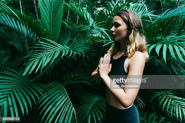 Woman doing yoga in tropical forest