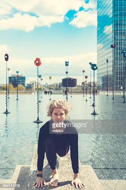 Femme faisant du yoga près du lac, dans un cadre urbain, Paris