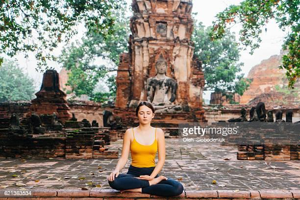 Woman doing yoga near the ruins of Buddha