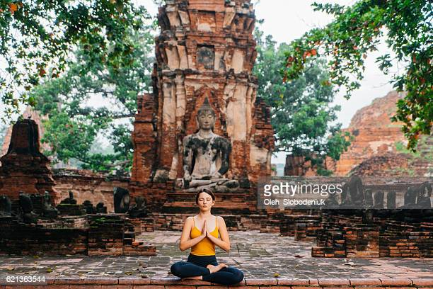 Woman doing yoga near the ruins of Buddhist Temple