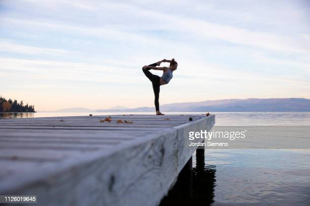 a woman doing yoga on a dock - yoga stockfoto's en -beelden