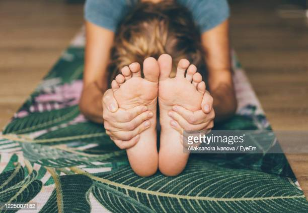 woman doing yoga on a yoga mat - barefoot stock pictures, royalty-free photos & images