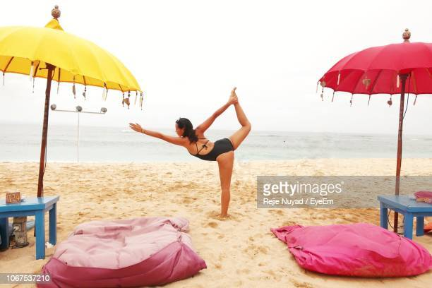 Woman Doing Yoga On Beach Against Sky