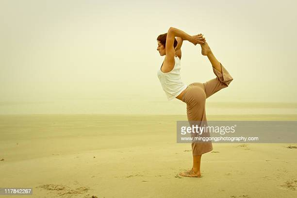 Woman doing yoga on beach at morning.
