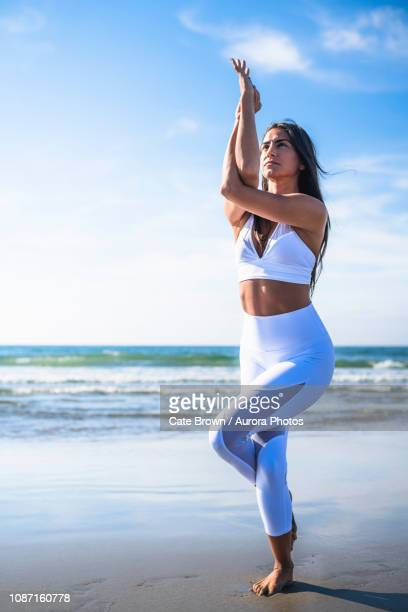 woman doing yoga on beach - tree position stock photos and pictures