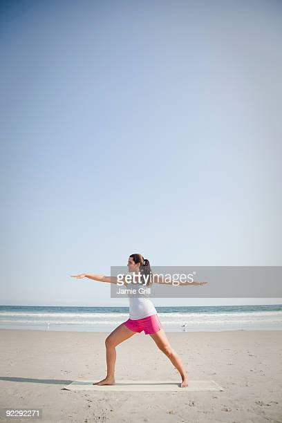 woman doing yoga on beach - rockaway peninsula stock pictures, royalty-free photos & images