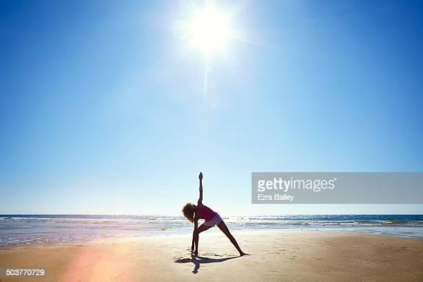 Woman doing yoga on deserted beach