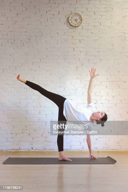 woman doing yoga on floor against wall - yogi stock pictures, royalty-free photos & images