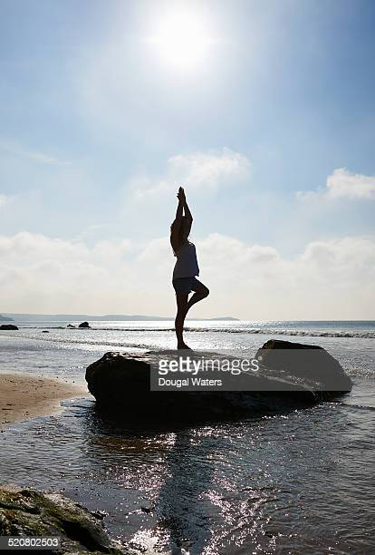 Woman doing yoga on rock at beach