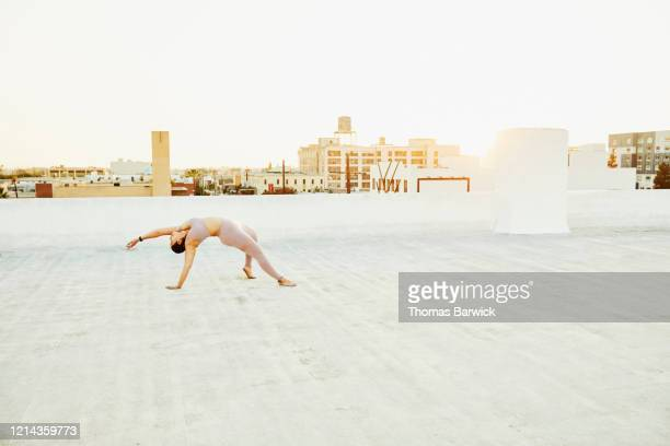 Woman doing yoga on rooftop at sunset