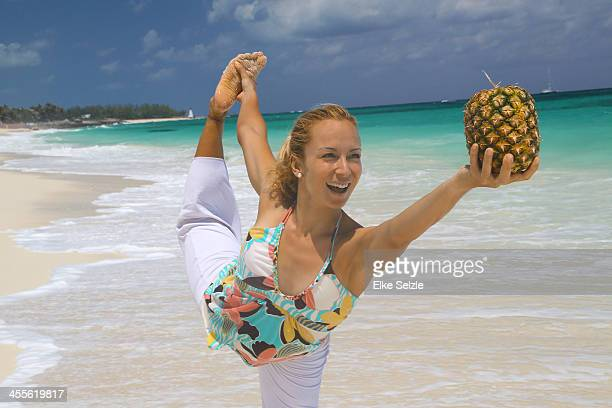 woman doing yoga on the beach holding pineapple - soles pose stock pictures, royalty-free photos & images