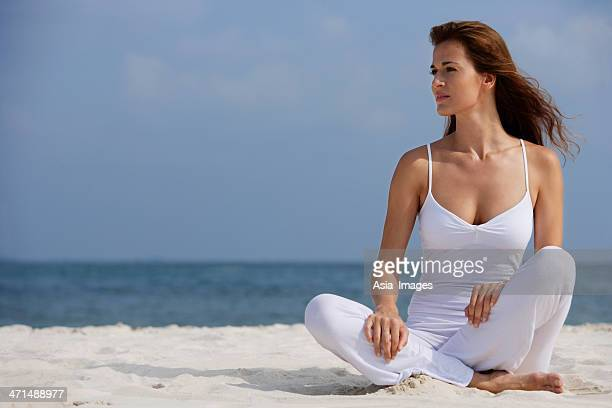 woman doing yoga on the beach - cleavage stock pictures, royalty-free photos & images
