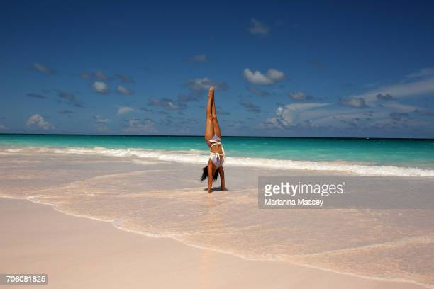 woman doing yoga on the beach - monokini photos et images de collection