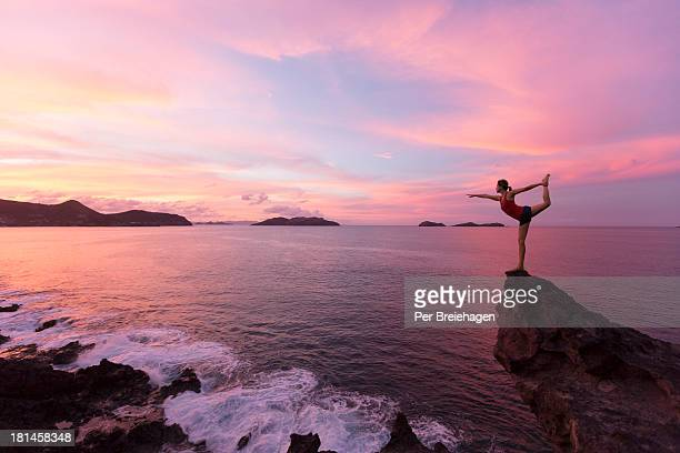 a woman doing yoga on the edge of a cliff - フランス海外領 ストックフォトと画像