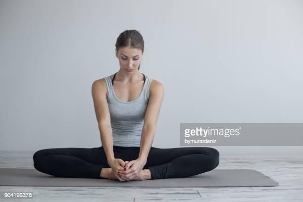 mujer haciendo yoga en el piso - piernas cruzadas fotografías e imágenes de stock