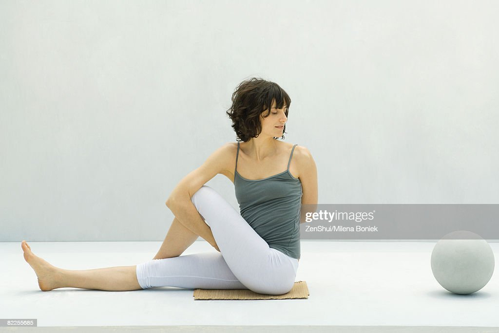 Woman doing yoga on the ground, ball nearby : Stock Photo
