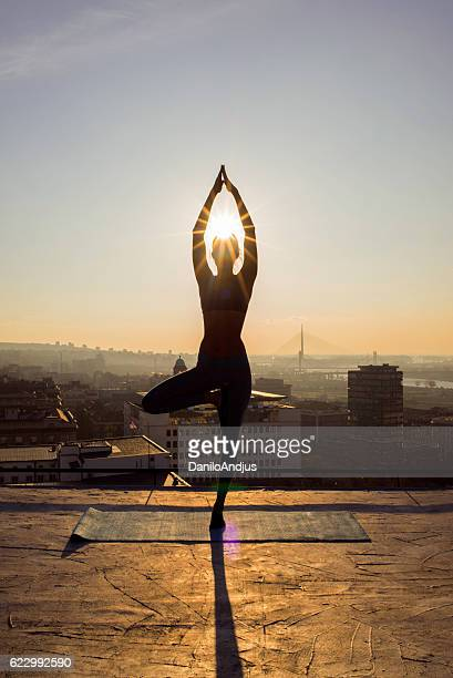 woman doing yoga on the rooftop on sunset