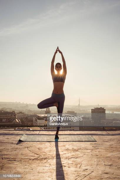 woman doing yoga on the rooftop - holy city stock pictures, royalty-free photos & images