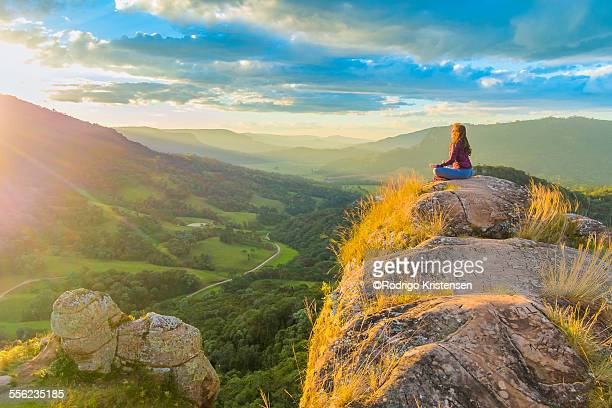 Woman doing yoga on top of the mountains.