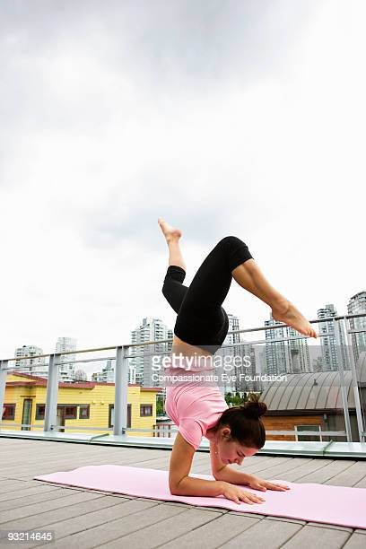 woman doing yoga outside with city line behind