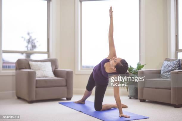 Woman doing yoga pose inside