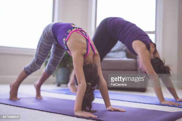 Woman doing yoga pose inside with daughter
