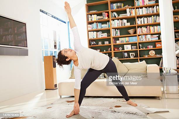 woman doing yoga streches in livingroom. - curly hair stock pictures, royalty-free photos & images
