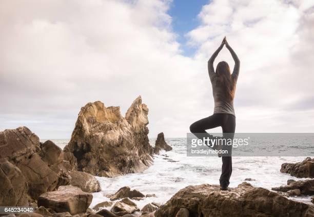 Woman doing yoga tree pose and meditating on rocky beach
