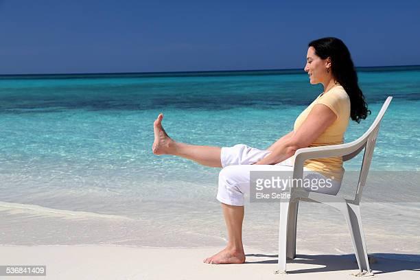 Woman doing Yoga with chair on beach