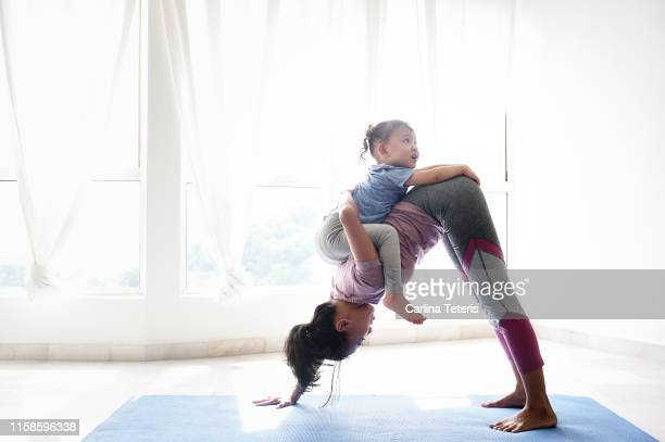 woman doing yoga with daughter on her back - sports training stock pictures, royalty-free photos & images