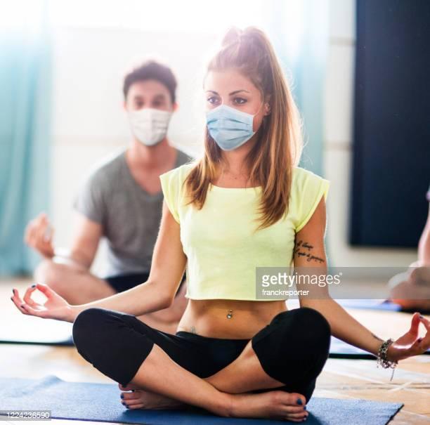 frau macht yoga mit gesichtsmaske - turner syndrome stock-fotos und bilder