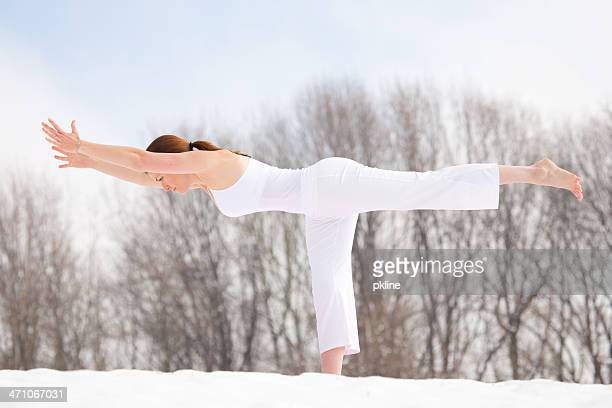 Woman doing Yogic 'Warrior 3' Pose in the snow
