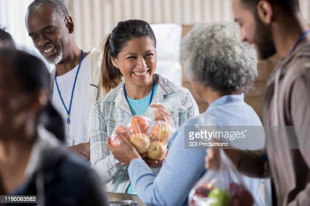 woman donates apples during food drive - food bank stock pictures, royalty-free photos & images