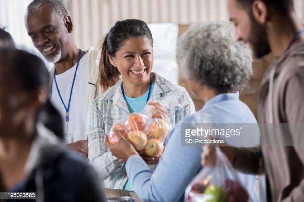 kvinnan donerar äpplen under food drive - matbank bildbanksfoton och bilder