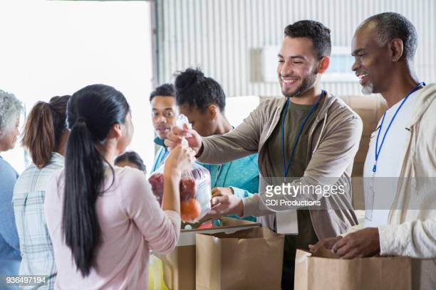 woman donates bag of fruit to food bank - community volunteer stock pictures, royalty-free photos & images