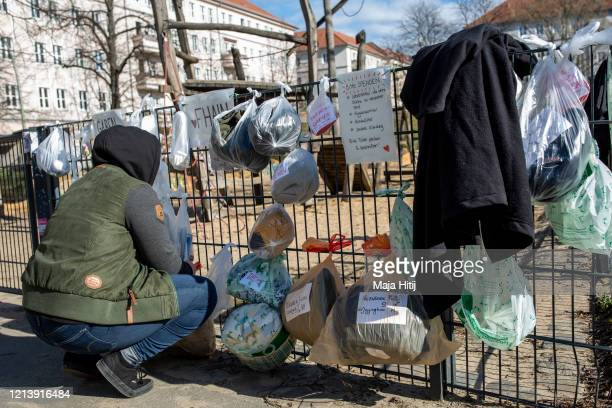 Woman donates bags with clothes and food in park in Friedrichshain neighborhood for the homeless on March 21, 2020 in Berlin, Germany. Everyday life...