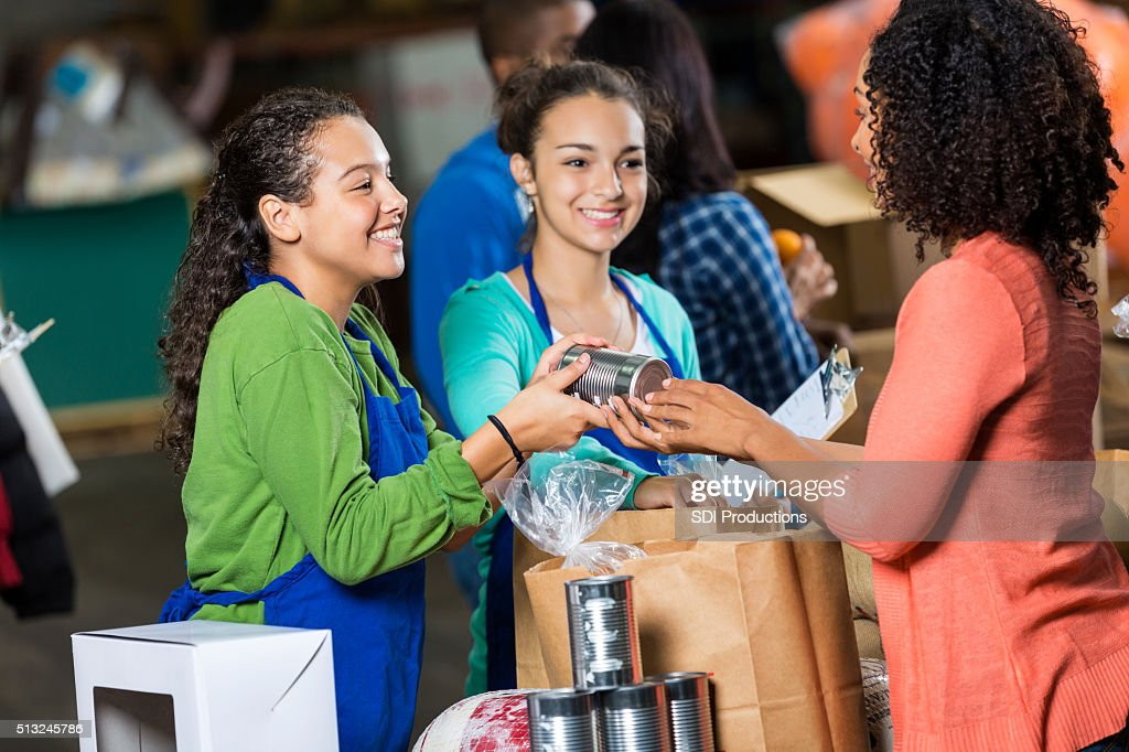 Woman donates canned goods to charity : Stock Photo