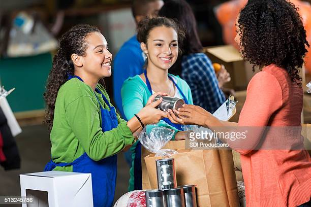 woman donates canned goods to charity - donation box stock pictures, royalty-free photos & images
