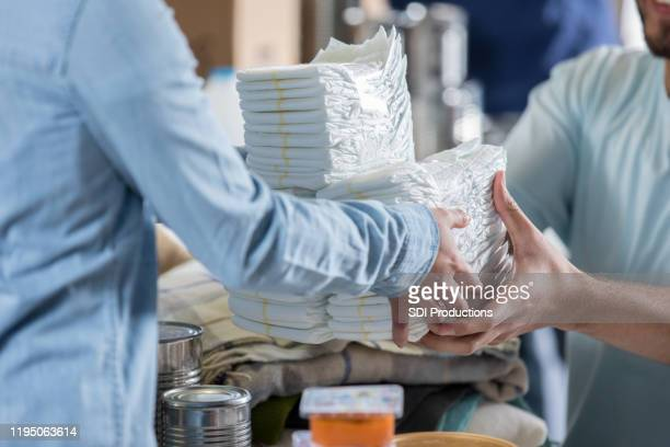 woman donates diapers during clothing drive - diaper stock pictures, royalty-free photos & images