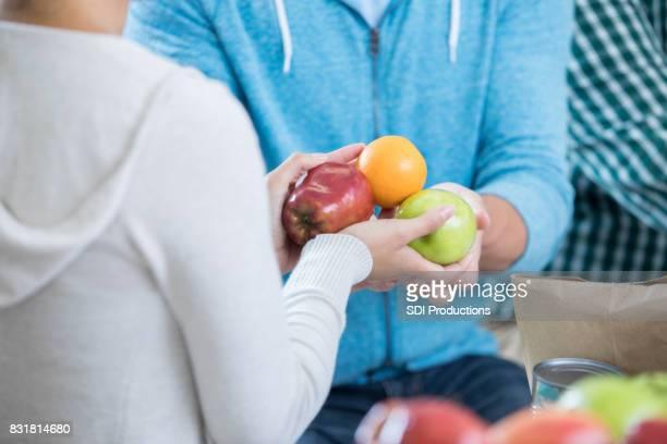 Frau spendet frisches Obst an Food bank