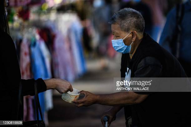 Woman donates money to a person begging in the Sham Shui Po district of Kowloon in Hong Kong on January 27 one of the international business hub's...