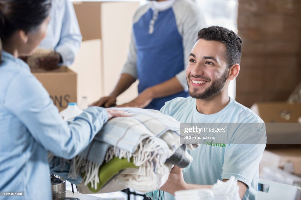Woman donates warm clothing during clothing drive : Stock Photo