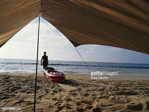woman dragging kayak towards ocean, view from beneath tarp - 防水シート ストックフォトと画像