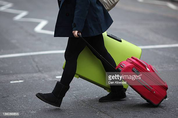 Woman drags her suitcases towards Victoria Coach Station on December 23, 2011 in London, England. The AA estimates 18 million vehicles will be...