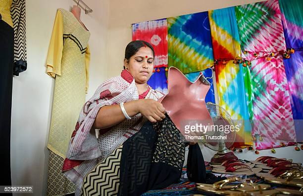 Woman draped a dress in her own shop on a rural market on April 10, 2016 in Narikelbari, Bangladesh.