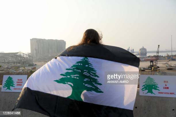 Woman, draped in a black-striped Lebanese flag, looks at the site of the massive explosion at Beirut's port area, during a demonstration to mark one...