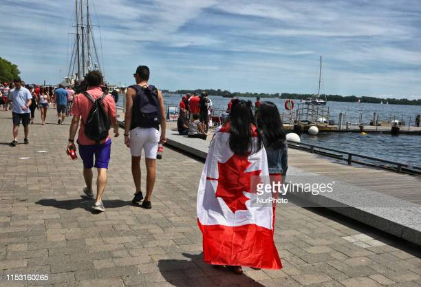 Woman draped in a Canadian flag walks along the path near Lake Ontario during the 152nd Canada Day celebration in Toronto Ontario Canada on July 01...
