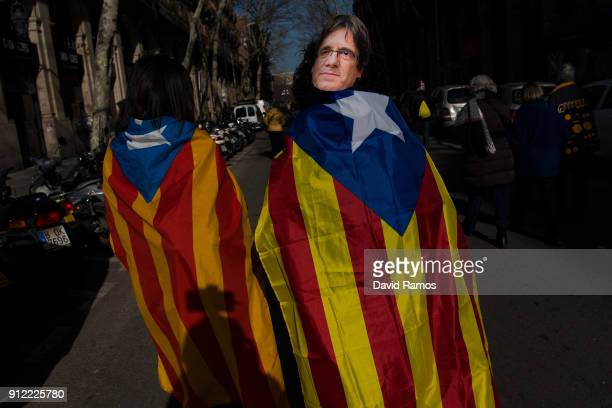 A woman draped in a Catalonia's Proindependence flag know as 'Estelada' and wearing a cutout mask of the former Catalan President Carles Puigdemont...