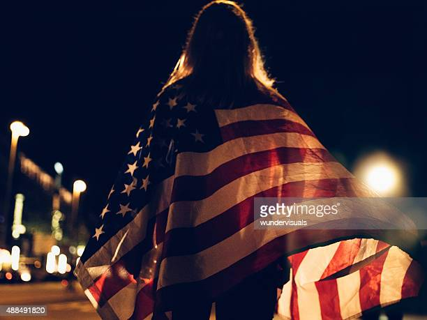 Woman draped with American flag on city street at night